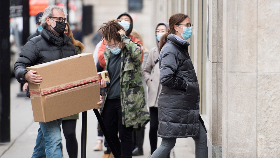 People wear face masks as they enter a store in Montreal, Saturday, November 14, 2020, as the COVID-19 pandemic continues in Canada and around the world. THE CANADIAN PRESS/Graham Hughes