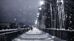 A pedestrian walks across Alexandra Bridge during snowfall.  (Photo by Marc-Olivier Jodoin of Unsplash)