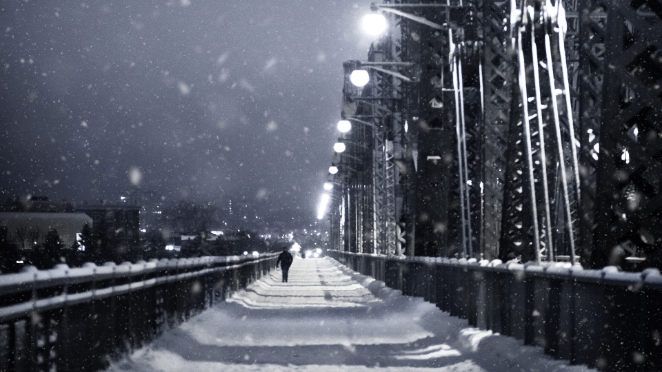 A pedestrian walks across Alexandra Bridge during snowfall.  (Photo by Marc-Olivier Jodoin of Unsplash)