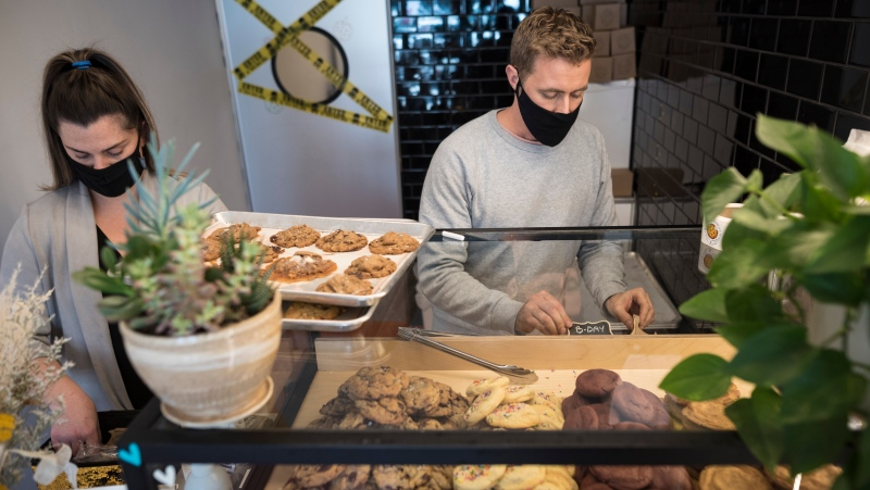 Chelsea Hearty, left, and Ian Moores, the proprietors of Courage Cookies, prepare to open their pop-up shop in Toronto on Saturday, October 24, 2020. THE CANADIAN PRESS/Tijana Martin