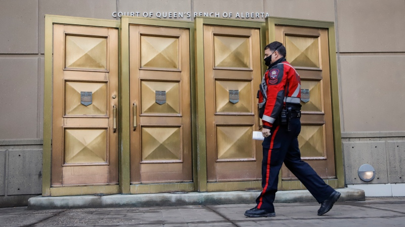 A police officer wears a mask as he enters the Calgary Courts Centre in Calgary, Alta., Friday, Oct. 30, 2020, amid a worldwide COVID-19 pandemic. THE CANADIAN PRESS/Jeff McIntosh