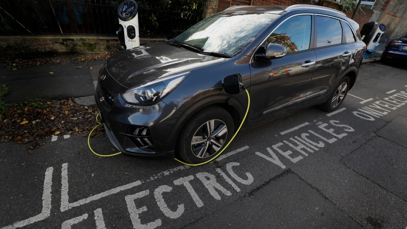 "An electric car charges on a street recharging port in London, Wednesday, Nov. 18, 2020. Britain says it will ban the sale of new gasoline and diesel cars by 2030, a decade earlier than its previous commitment. Prime Minister Boris Johnson made the pledge Tuesday as part of plans for a ""green industrial revolution"" that he claims could create up to a 250,000 jobs in energy, transport and technology. (AP Photo/Kirsty Wigglesworth)"
