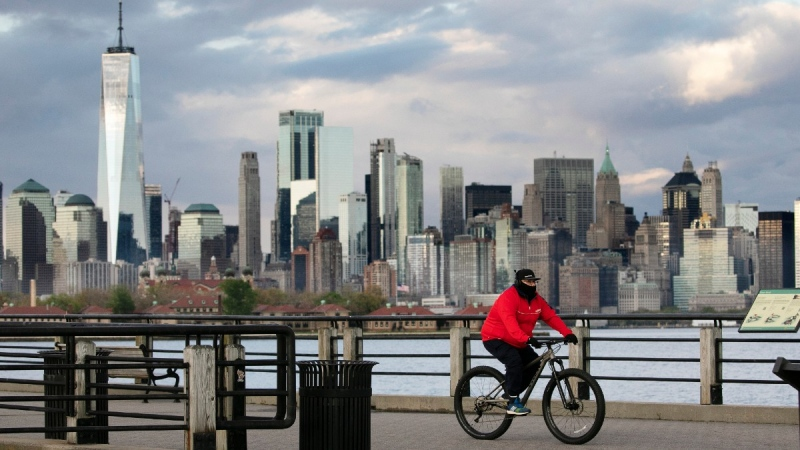 A cyclist wears a mask as he bikes in Liberty State Park in Jersey City, N.J., on May 11, 2020. (Mark Lennihan / AP)