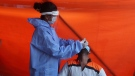 A health worker takes a nasal swab sample of a man to test for COVID-19 in Mumbai, India, Thursday, Nov. 19, 2020. (AP Photo/Rafiq Maqbool)