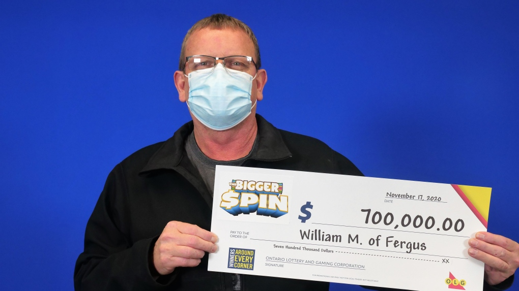 A man holds a cheque for $700,000