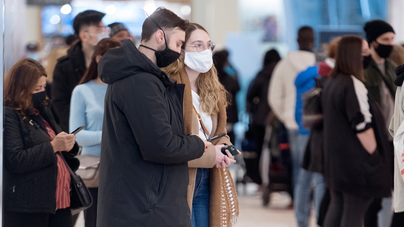 People wear face masks as they wait to enter a store in a shopping mall in Montreal, Saturday, November 14, 2020, as the COVID-19 pandemic continues in Canada and around the world. (THE CANADIAN PRESS/Graham Hughes)