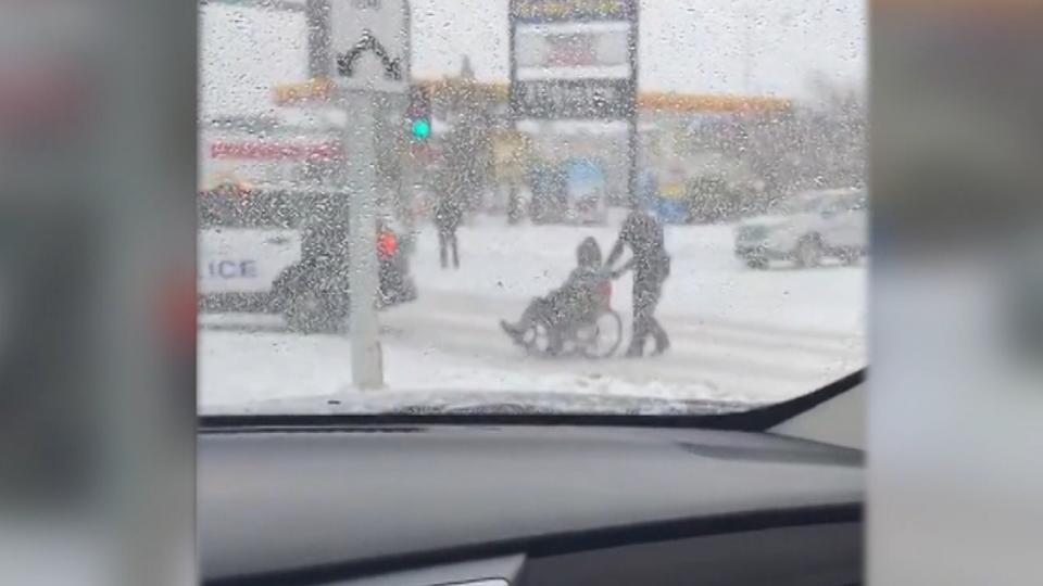 An Edmonton police officer was caught on camera helping a person in a wheelchair get across a snowy street.