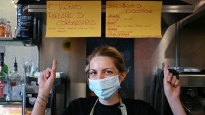 Cristina Mattioli, manager of the Feeling bar, put up one poster banning virus talk and another offering other ideas for conversation. (Alberto Pizzoli/AFP)
