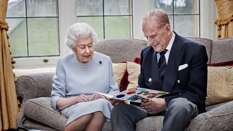 Queen Elizabeth II and Prince Philip, Duke of Edinburgh look at a homemade wedding anniversary card, given to them by their great grandchildren Prince George, Princess Charlotte and Prince Louis, as the royal couple sit in the Oak Room at Windsor Castle, England, Nov. 17, 2020, ahead of their 73rd wedding anniversary. Elizabeth married Philip on Nov. 20, 1947, at Westminster Abbey in London. (Chris Jackson/Pool via AP)