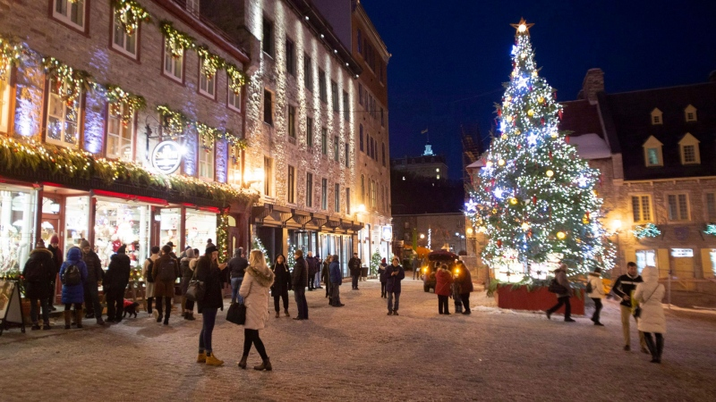 People walk to Place Royale where a giant Christmas tree is illuminated in the old historic area of Quebec City, Sunday, Dec. 16, 2018. THE CANADIAN PRESS/Jacques Boissinot