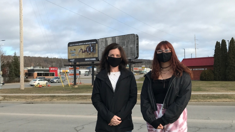 Erin Celebre, MADD Nipissing Chapter President and 14-year-old billboard designer Taylor Laing stand in front of the billboard on Mckeown Avenue and Champlain Street in North Bay. Nov.21/20 (Alana Pickrell/CTV News Northern Ontario)