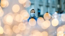 A man wears a face mask as he walks by festive lights in Montreal, Saturday, Nov. 21, 2020, as the COVID-19 pandemic continues in Canada and around the world. THE CANADIAN PRESS/Graham Hughes