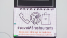 A billboard at Four Crowns Inn can be seen displaying the #saveMBrestaurants hashtag.