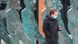 A pedestrian wearing a mask checks his mobile device while waiting to cross a street in Calgary, Alta., Thursday, Nov. 19, 2020, amid a worldwide COVID-19 pandemic. THE CANADIAN PRESS/Jeff McIntosh