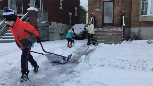 An Ottawa family clears snow from their walkway in Wellington Village in December 2020. (Jim O'Grady/CTV News Ottawa)