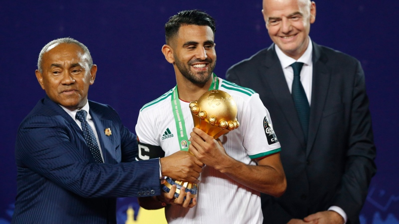 Algeria's Riyad Mahrez, centre, holds the Cup with Confederation of African Football president Ahmad Ahmad of Madagascar, as FIFA president Gianni Infantino, back, looks on during the African Cup of Nations final soccer match between Algeria and Senegal in Cairo International stadium in Cairo, Egypt, Friday, July 19, 2019. v won 1-0. (AP Photo/Ariel Schalit)