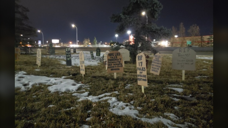 Cardboard grave markers across the street from Health Minister Tyler Shandro's office in southwest Calgary on Monday morning (Twitter/ @lizzyinyyc)