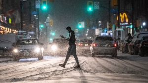 A person crosses Elgin Street as snow falls in Ottawa, on Sunday, Nov. 22, 2020. Environment Canada has issued a snowfall warning, with amounts of 15 to 20 cm expected by Monday morning. (Justin Tang/THE CANADIAN PRESS)