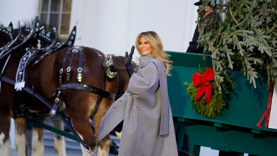 First lady Melania Trump waves as she stands next to the 2020 Official White House Christmas tree as it is presented on the North Portico of the White House, Monday, Nov. 23, 2020, in Washington. (AP Photo/Andrew Harnik)