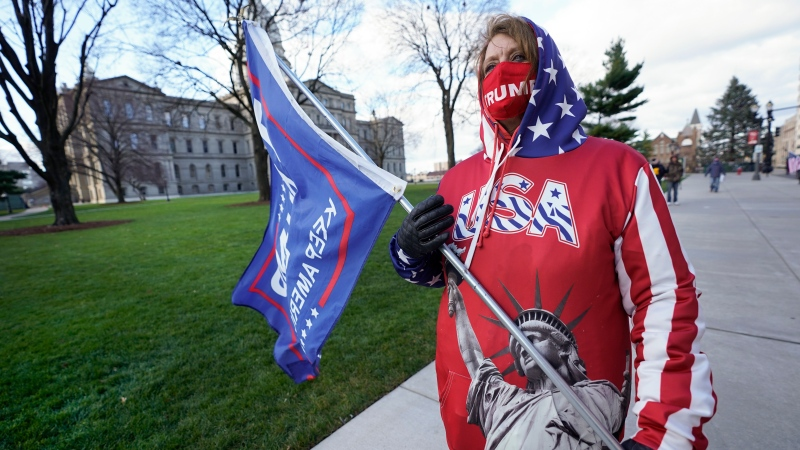 Lisa McClain, a President Trump supporter, walks near the Capitol building in Lansing, Mich., Monday, Nov. 23, 2020. (AP Photo/Paul Sancya)