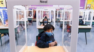 FILE - Children wearing masks sit behind screened in cubicles as they learn in their classroom after getting their pictures taken at picture day at St. Barnabas Catholic School during the COVID-19 pandemic in Scarborough, Ont., on Tuesday, October 27, 2020. THE CANADIAN PRESS/Nathan Denette