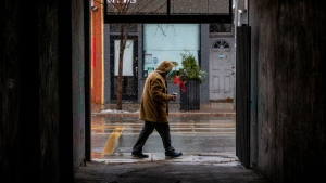 A man walks along Queen Street West as snow falls in Toronto on Sunday, November 22, 2020. THE CANADIAN PRESS/Carlos Osorio
