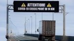 A sign indicates that provincial health department workers will stop traffic that has crossed the Confederation Bridge in Cape Jourimain, N.B., Sunday, March 22, 2020. Prince Edward Island is reporting two new cases of COVID-19, including one involving a child under the age of 10. THE CANADIAN PRESS/Andrew Vaughan