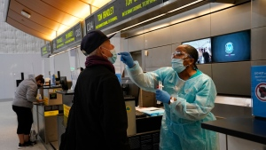 Licensed vocational nurse Caren Williams, left, collects a nasal swab sample from a traveler at a COVID-19 testing site at the Los Angeles International Airport in Los Angeles, Monday, Nov. 23, 2020. (AP Photo/Jae C. Hong)