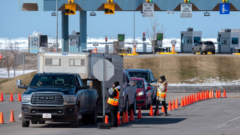 Provincial health department workers stop traffic that has crossed the Confederation Bridge in Borden-Carleton, P.E.I. on Sunday, March 22, 2020. Prince Edward Island has announced an exemption that will allow Canadians with family in need of support to travel to the Island on compassionate grounds. THE CANADIAN PRESS/Andrew Vaughan