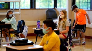Students in fifth grade wear masks as they wait for their teacher in the classroom at Oak Terrace Elementary School in Highwood, Ill., part of the North Shore school district, on Thursday, Sept. 3, 2020. An analysis conducted by The Associated Press and Chalkbeat shows that race is a strong predictor of which public schools are offering in-person instruction to start the year and which aren't. (AP Photo/Nam Y. Huh)