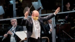 Musical director Riccardo Frizza, wearing a face mask to curb the spread of COVID-19, directs the orchestra during rehearsals for Gaetano Donizetti's opera, Marino Faliero, at the Donizetti theatre in Bergamo, Italy, Thursday, Nov. 18, 2020. (Gianfranco Rota/Teatro Donizetti via AP)