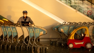 A worker wearing a face mask and face shield to protect against the coronavirus collects luggage carts at the Beijing Daxing International Airport in Beijing, Tuesday, Nov. 24, 2020. (AP Photo/Mark Schiefelbein)