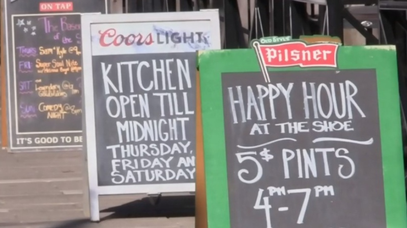 Signs are seen outside bars and restaurants in downtown Halifax in this file photo.