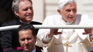 Pope Benedict XVI, right, arrives in St. Peter's square at the Vatican for a general audience as his then-butler Paolo Gabriele, bottom, and his personal secretary Georg Gaenswein sit in the car with him, on May 2, 2012. (Alessandra Tarantino / AP)