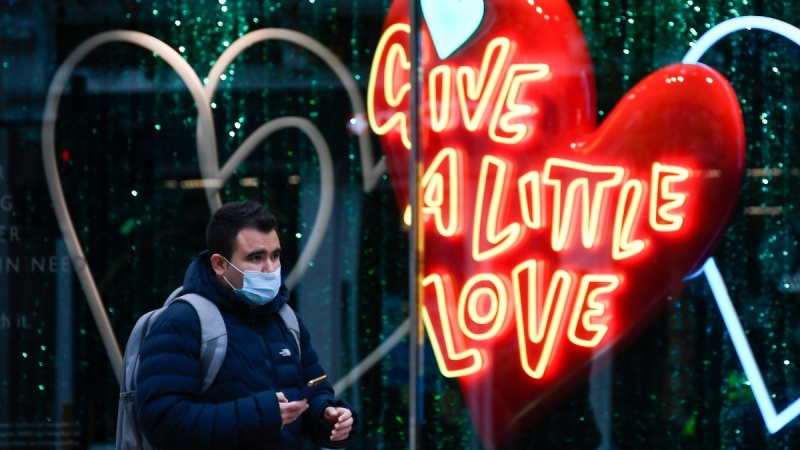 A man wears a face mask as he walks past a shop window in Oxford Street, in London, on Nov. 24, 2020. (Alberto Pezzali / AP)