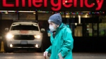 A woman wears a protective face mask to help prevent the spread of COVID-19 as they walk past the emergency department of the Vancouver General Hospital in Vancouver Wednesday, Nov. 18, 2020. (Jonathan Hayward / THE CANADIAN PRESS)