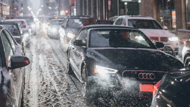 Vehicles commuting through snowy city streets.