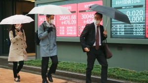 People walk by an electronic stock board of a securities firm showing Japan's Nikkei 225 index in Tokyo, Wednesday, Nov. 25, 2020. (AP Photo/Koji Sasahara)