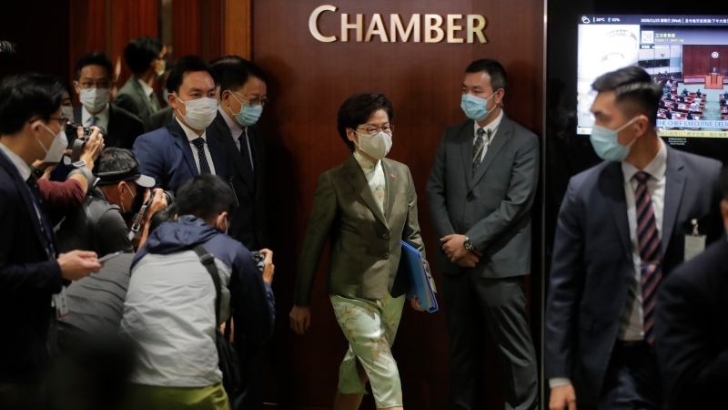 Hong Kong Chief Executive Carrie Lam, centre, leaves after delivering her policies at chamber of the Legislative Council in Hong Kong, Wednesday, Nov. 25, 2020. (AP Photo/Kin Cheung)