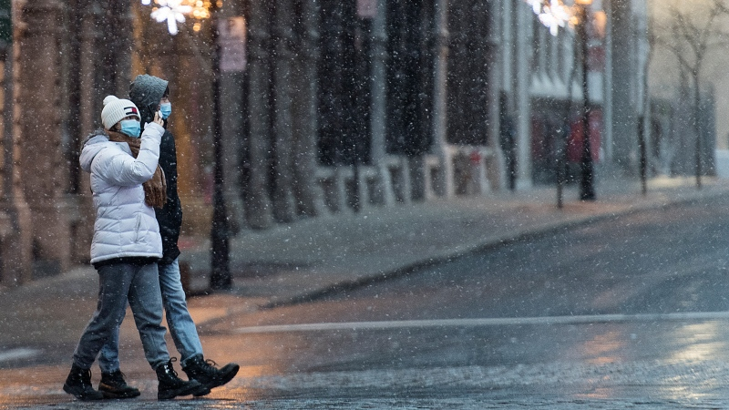 People wear face masks as they walk along a street as light snow falls in Montreal, Sunday, November 22, 2020, as the COVID-19 pandemic continues in Canada and around the world. THE CANADIAN PRESS/Graham Hughes
