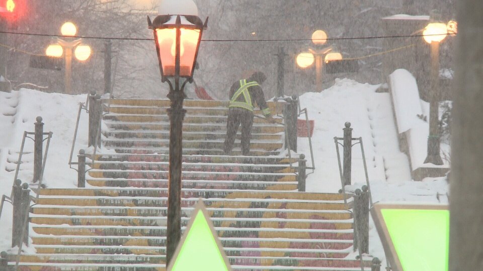 A worker clears snow from a staircase during a snowfall in Ottawa. Nov. 25, 2020. (Jim O'Grady / CTV News Ottawa)