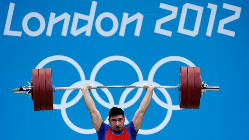 In this Tuesday, July 31, 2012 file photo, Razvan Constantin Martin of Romania competes during the men's 69-kg, group A, weightlifting competition at the 2012 Summer Olympics, in London. Two Romanian weightlifters have been stripped of their 2012 London Olympics medals for positive tests for steroids. It brings London's record total of doping cases at any Summer or Winter Games to 77. The International Olympic Committee says silver medalist Roxana Cocos and bronze medalist Razvan Martin tested positive for multiple steroids in reanalysis of their samples. (AP Photo/Hassan Ammar)