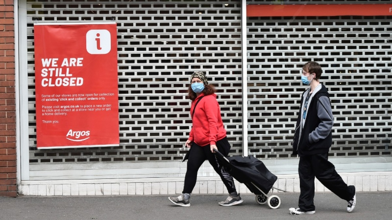 Members of the public walk past a closed shop in Leicester city centre, England, on June 30, 2020. (Rui Vieira / AP)