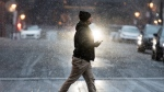 A man walks along a street as light snow falls in Montreal, Sunday, November 22, 2020, as the COVID-19 pandemic continues in Canada and around the world. THE CANADIAN PRESS/Graham Hughes