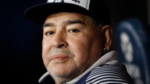 In this March 7, 2020 file photo, Diego Maradona, coach of Gimnasia y Esgrima, sits on the bench prior to Argentina's soccer league match against Boca Juniors at La Bombonera stadium in Buenos Aires, Argentina. (AP Photo/Natacha Pisarenko, File)