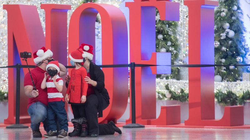 People wear face masks as they pose next to a Christmas display in Montreal, Sunday, November 22, 2020, as the COVID-19 pandemic continues in Canada and around the world. THE CANADIAN PRESS/Graham Hughes