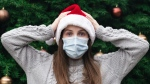 A woman holding her hands on her head while wearing a Santa hat and mask in front of a tree decorated for the holidays. (Photo by Volodymyr Hryshchenko on Unsplash)