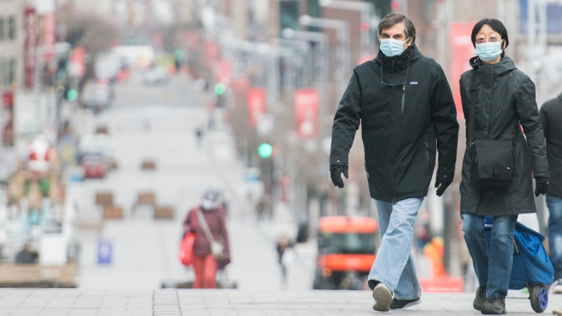People wear face masks as they walk along a street in Montreal, Sunday, November 22, 2020, as the COVID-19 pandemic continues in Canada and around the world. THE CANADIAN PRESS/Graham Hughes
