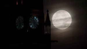 The moon is seen setting behind the Parliament buildings Monday November 14, 2016 in Ottawa. THE CANADIAN PRESS/Adrian Wyld