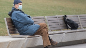 A man wears a face mask as he sits on a city bench in Montreal, Sunday, November 22, 2020, as the COVID-19 pandemic continues in Canada and around the world. THE CANADIAN PRESS/Graham Hughes